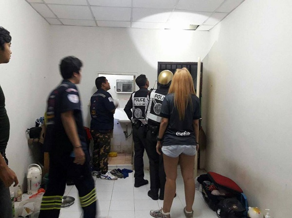 Officers shine a torch through into the ceiling where the rape suspect in hiding in Bangkok
