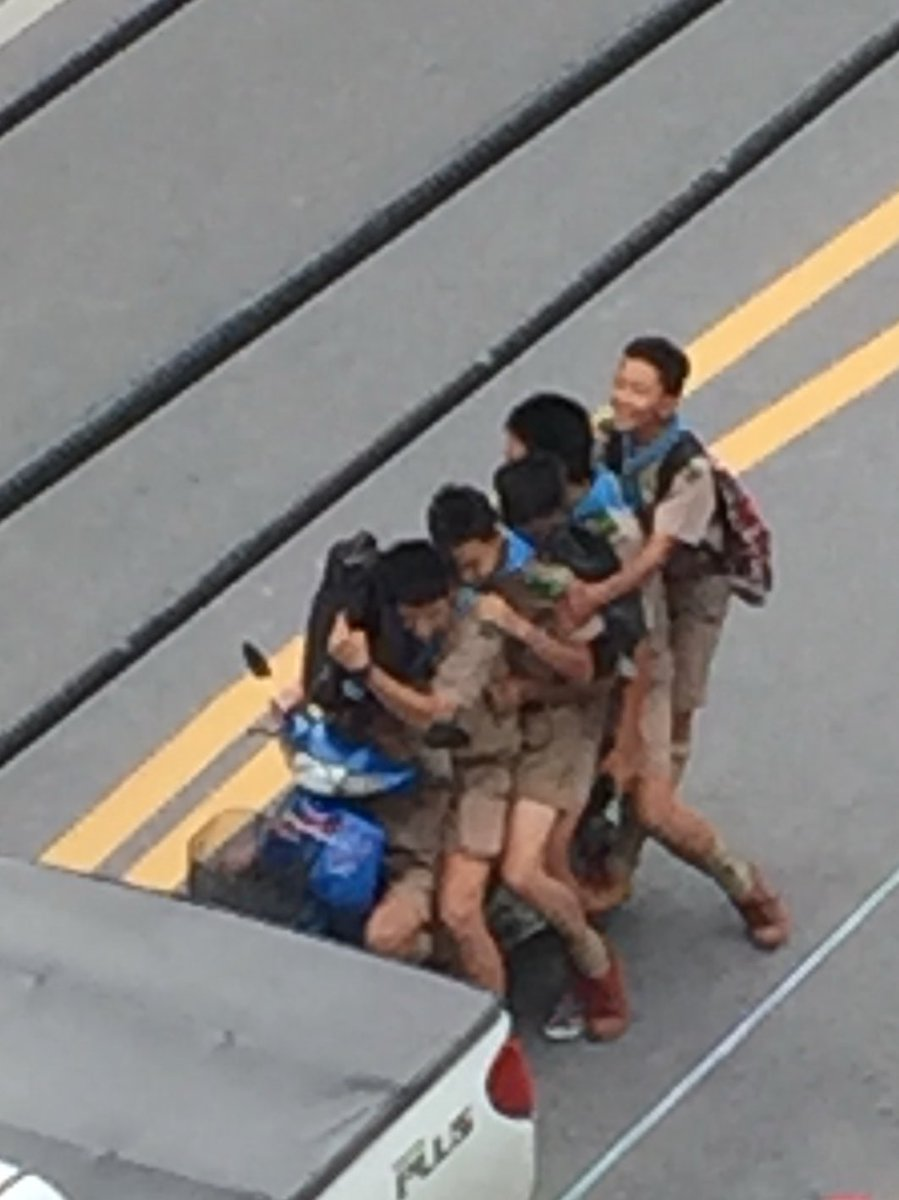 The youngsters ar in school uniform as they ride on the busy road in Phuket