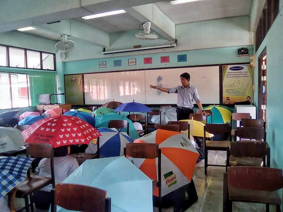 A teacher makes students hold umbrellas to stop them cheating during a test at a school in Hat Yai