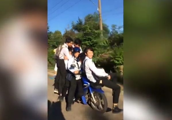 Seven kids riding on a motorcycle in Thailand