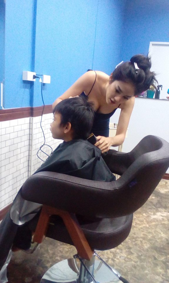 Nitchamon Jiraphoom cuts a young boy's hair with her cleavage on show
