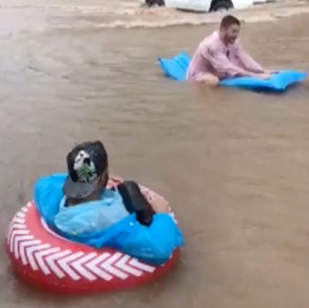 Brit tourists floating down a flooded street on lilos