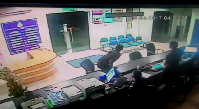 A policeman jumps from his seat when the station doors open by themselves