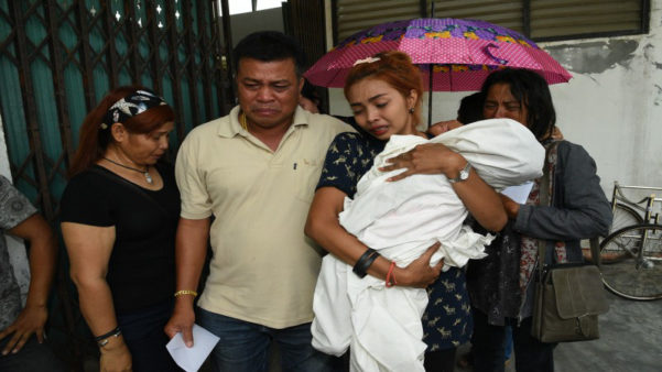 Heartbroken mother Jiranuch Trirat, 21, carries the body of her dead 11-month-old daughter Beta today after her boyfriend hanged her and himself live on Facebook yesterday in Phuket, Thailand