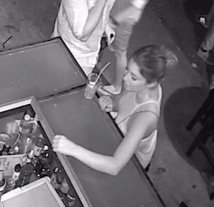 backpacker stealing drinks from behind the bar