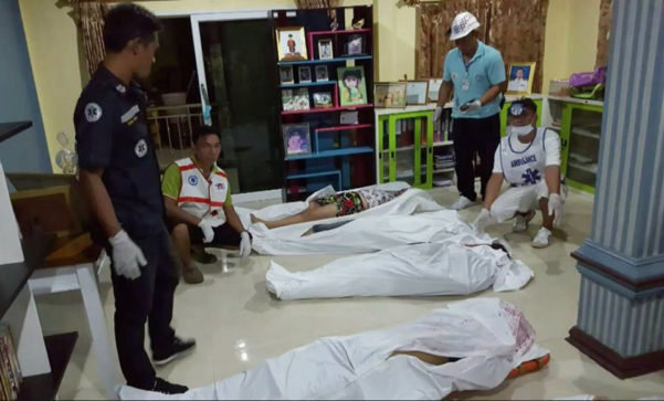 Police cover the bodies of a family executed by gunmen in Krabi