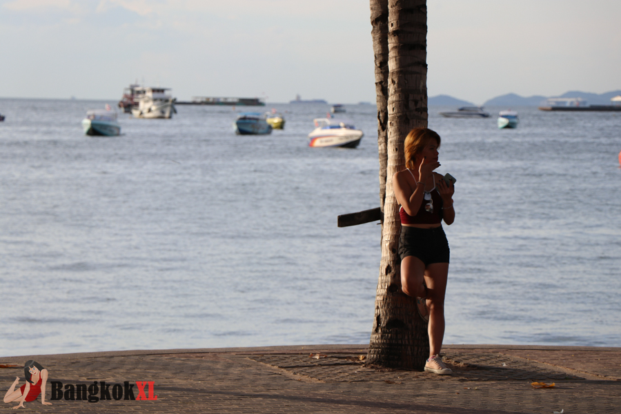 Beautiful dusk scene as this girl cats on her phone in front of the sea