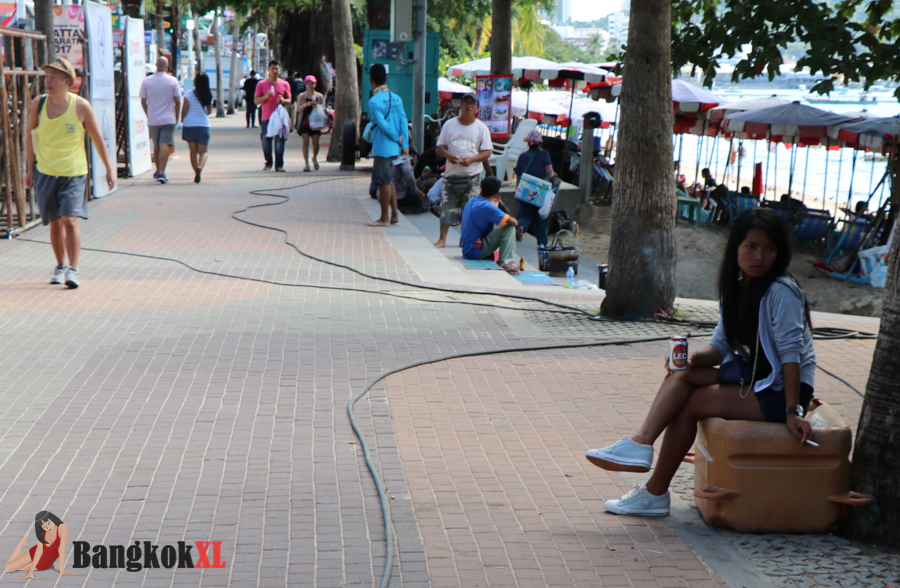 A girl smoking and drinking a Leo as she waits on Beach Road during the day