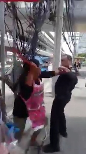 A furious fruit seller throws a huge shard of glass and waves a kitchen knife at council staff - after being told to move her stall.